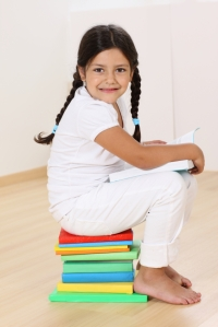 Little girl on a stack of books